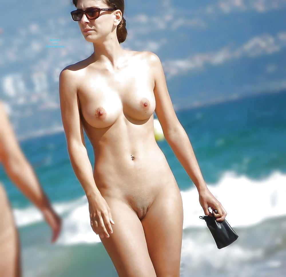 Naked sexy surfgirl with surfboard on tropical beach