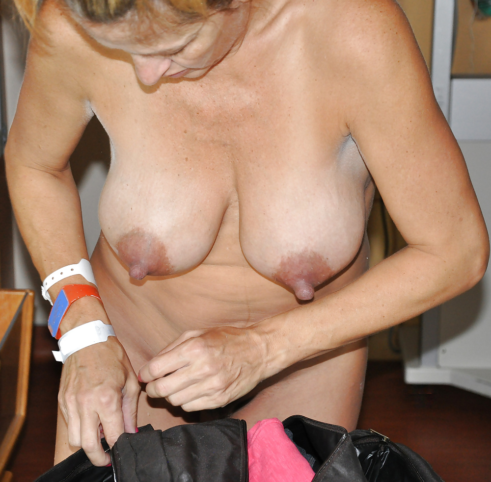 Naked mature woman with hands on breasts