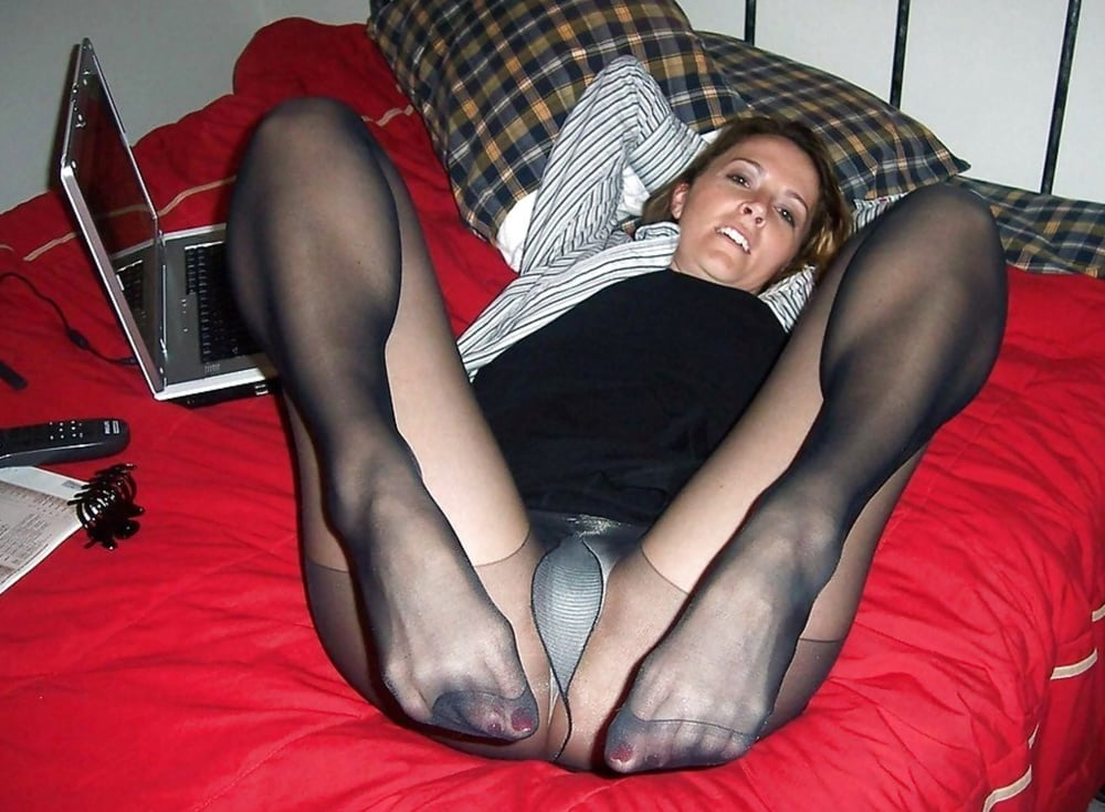 Young Girl Putting On Warm Stockings In Bed Stock Photo