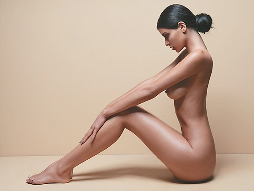 Nude woman wearing only high heeled shoes and a wristwatch